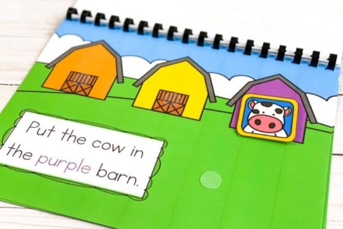 Overhead picture of a cow picture placed on a purple barn for the color matching farm theme activity.