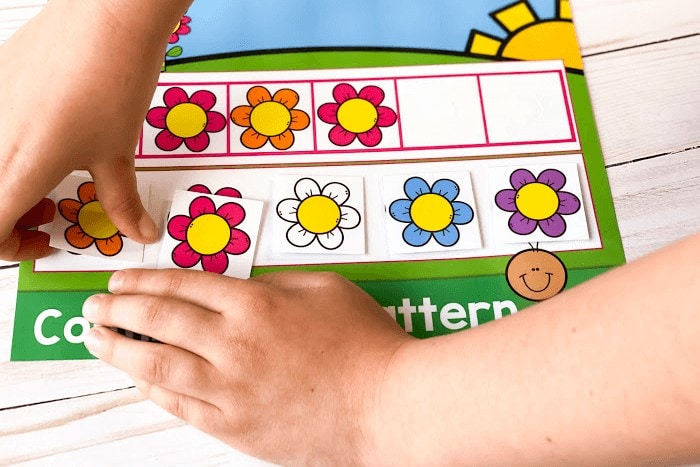 A child completing the printable spring flower theme AB pattern activity for the pattern orange-pink.